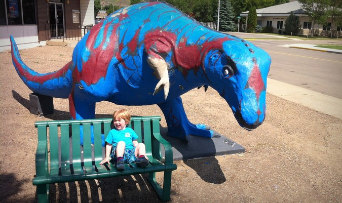 Baby crying near a dinosaur statue on vacation