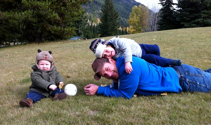 father and sons playing on the grass during their road trip