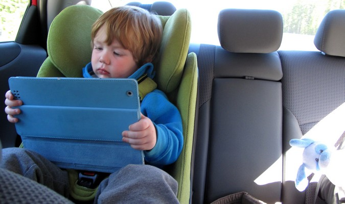 Toddler playing with electronics in the backseat on a family road trip
