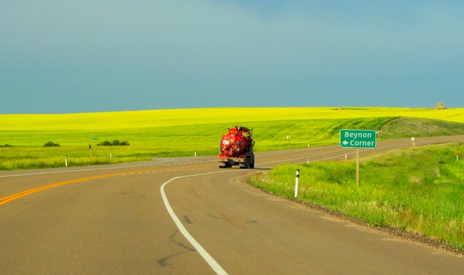 Red truck on an open road with a green feild in the countryside