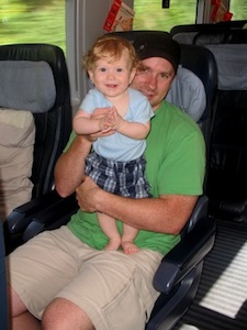 dad and son on a train traveling together