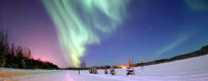 Northern lights in the snow landscape in Finland