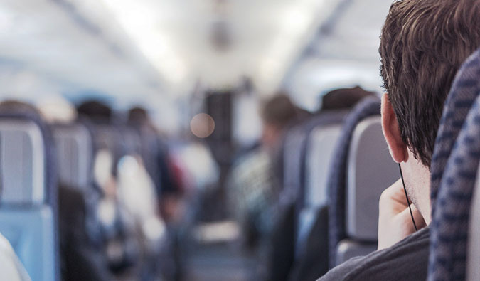 A man sitting in an airplane looking down the aisle at the flight attendant
