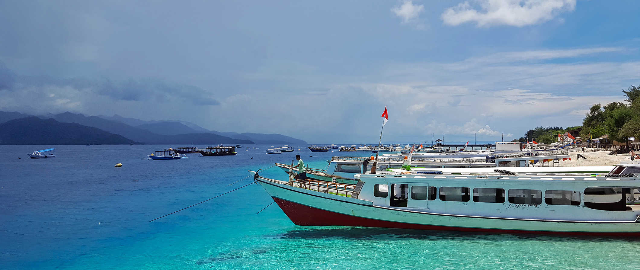 a beach with a boat in the Gili Islands