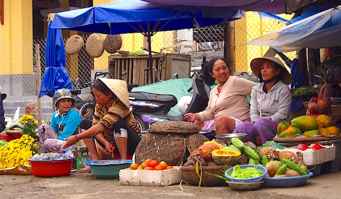 A group of local women at a market stall in Southeast Asia