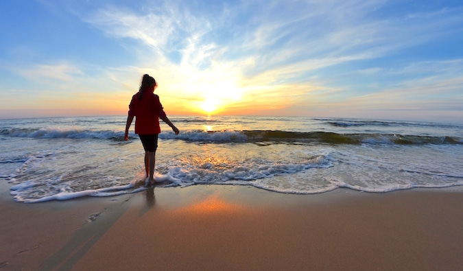 A lone woman walking barefoot on a picturesque beach