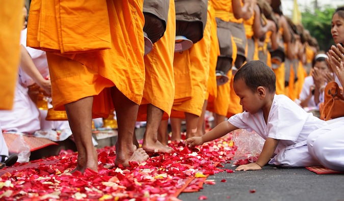 A child touching a bunch of rose petals that are laying at monks' feet