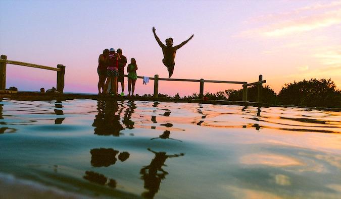travelers having fun jumping into water