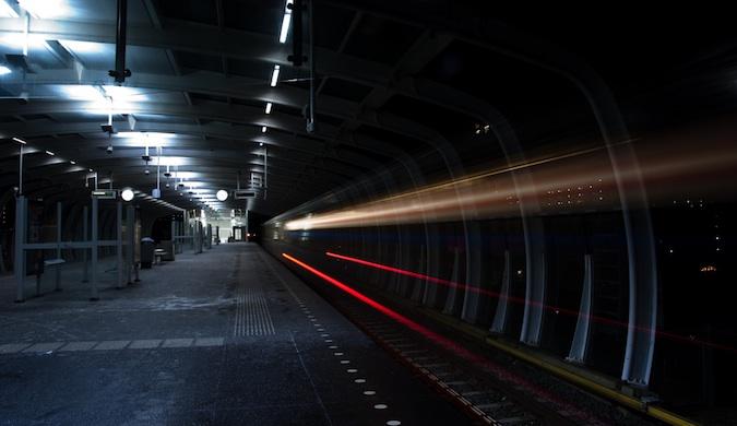 A long-exposure photo of a train speeding through a dark tunnel