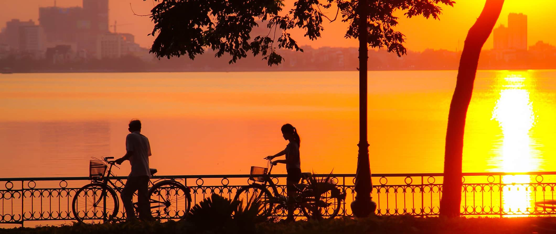 sunset and people on bikes in Hanoi