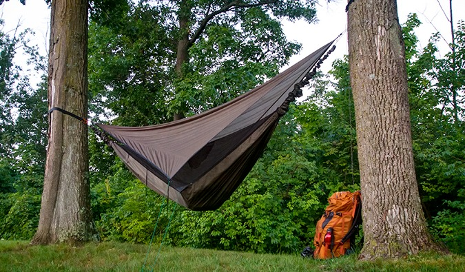 A hammock tied between two trees and a backpack sitting on the ground