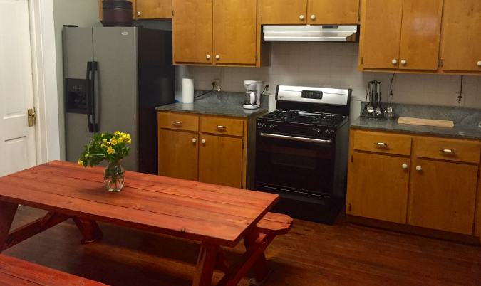 Hostel kitchen and dining table with flowers
