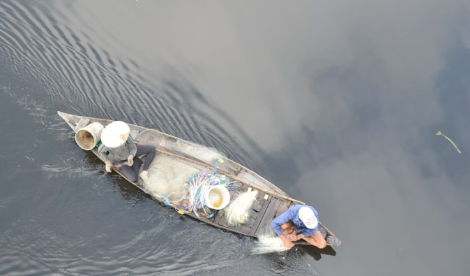 Fishing boat on the river in Vietnam's how an village, birds eye view