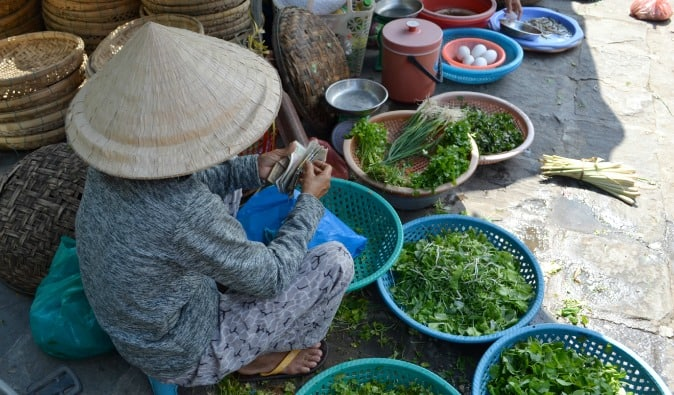 Old woman selling veggies at the vegetable market in Vietnam