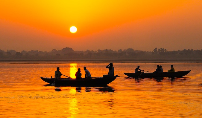 A golden sunset near a river with small fishing boats in India