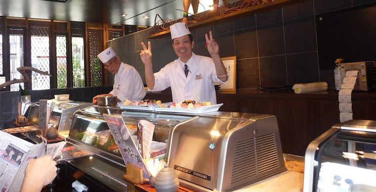 A Japanese sushi chef posing for a friendly photo from behind the counter