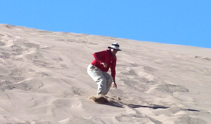 50 year old guy sand boarding down a sand dune