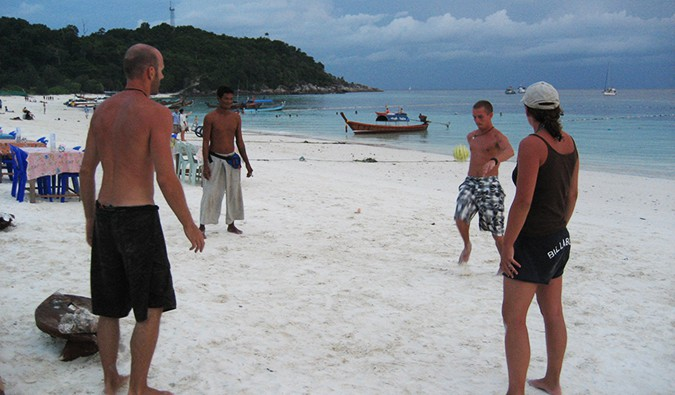 the group playing soccer on the beach in Ko Lipe