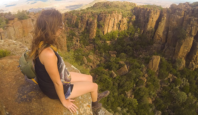 A nomadic solo female backpacker sitting on a cliff, taking in the view