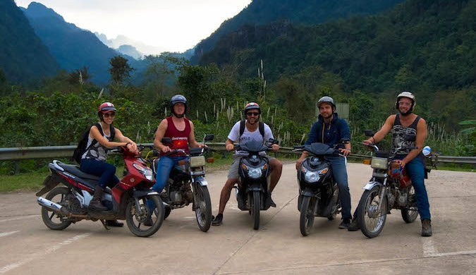Five people on motorbikes traveling in Southeast Asia