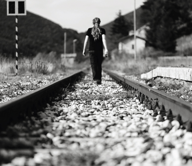 Black and white self-portrait of Laurence walking on railway tracks