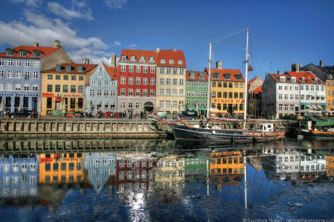 Photo of houses reflecting on the Nyhavn Harbor in Copenhagen, Denmark