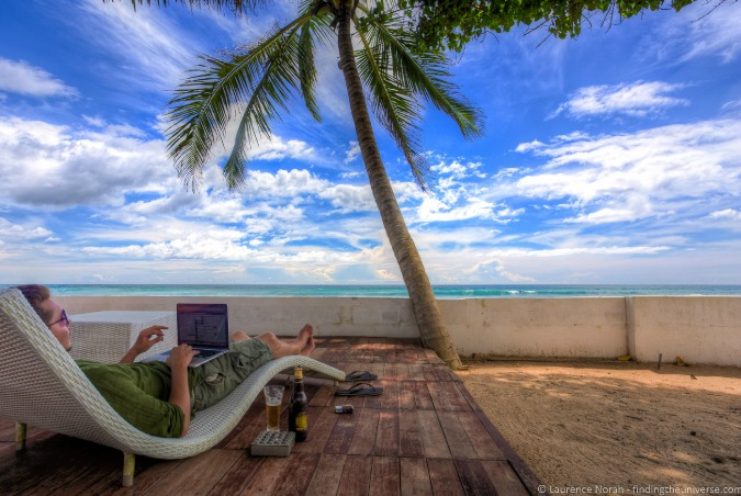 Remote worker working on a laptop beside a palm tree on a beach