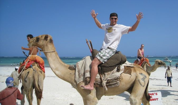 Lee Abbamonte riding a camel at the beach