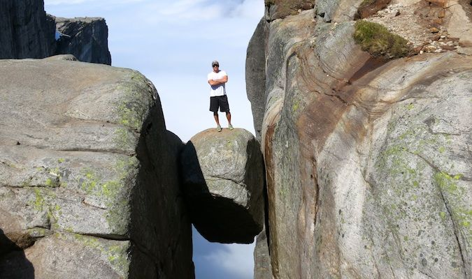 Lee Abbamonte standing on a large boulder in Norway