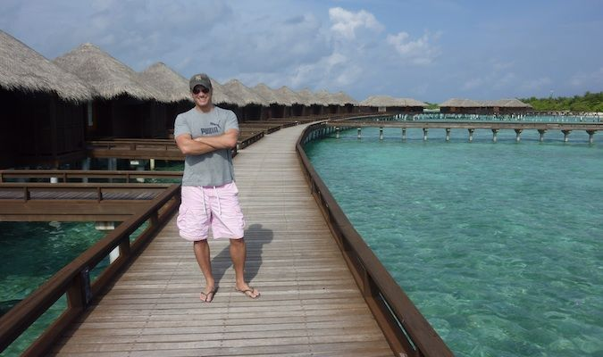 Lee Abbamonte standing on a long wooden dock in the Maldives