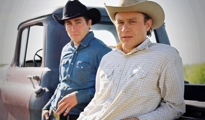 A two main characters from Brokeback Mountain standing beside their truck