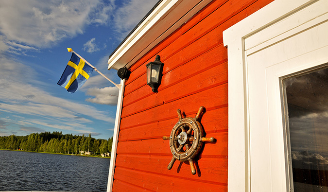 A typical Swedish cottage with a Swedish flag during the summer in Sweden