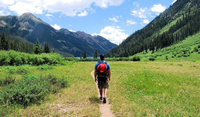 a backpacker hiking in beautiful meadow surrounded by mountains