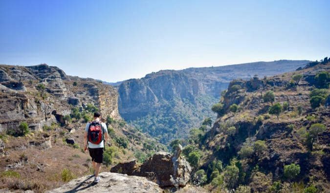 Nomadic Matt wearing a backpack and hiking near a cliff in Madagascar