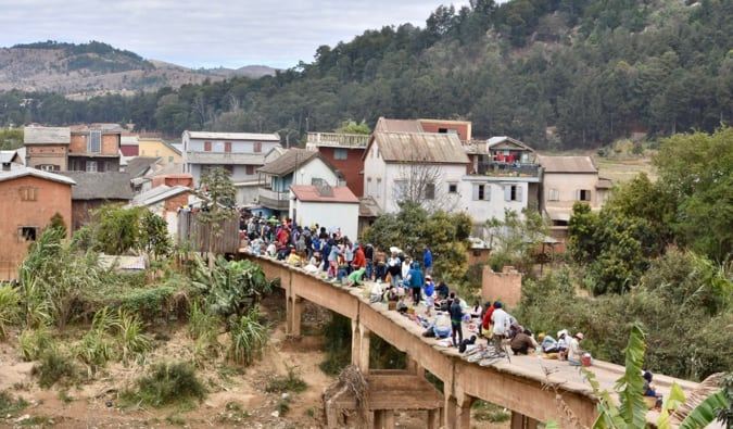 Locals crossing a narrow bridge during the day in Madagascar