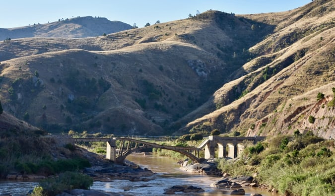 A collapsed bridge spanning a drying river in a valley in Madagascar