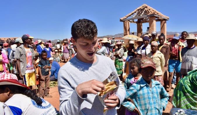 Nomadic Matt eating street food in a busy market in Madagascar