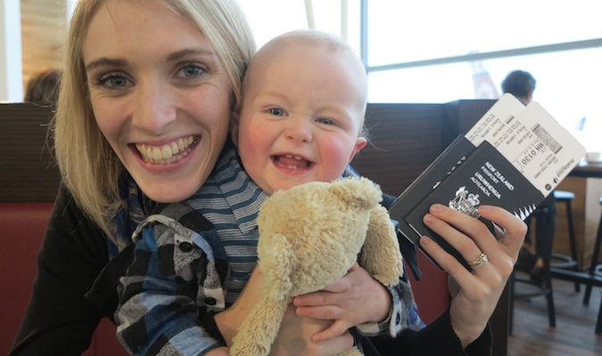 mom and baby son smiling with travel passports in hand