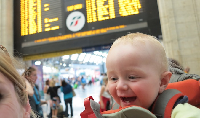 son in a baby carrier posing at a train station in Europe