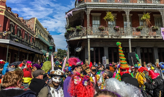 Mardi Gras attendees in costume on Bourbon Street