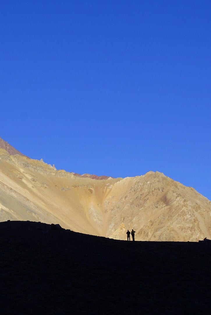 two people hiking in a sandy landscape in Mendoza