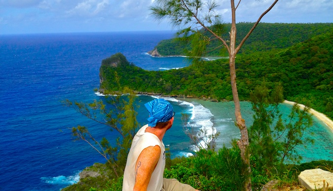 Michael looking at beautiful beach surrounded by lush jungle