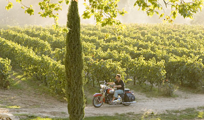 Russell Crowe riding a motorbike in the vineyard in A Good Year
