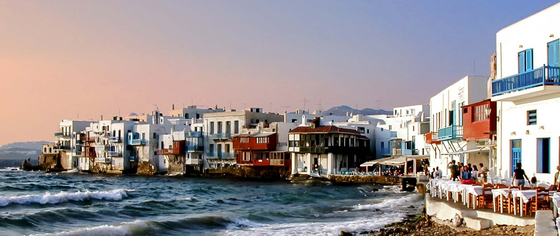 view of Mykonos buildings along the waterfront at sunset