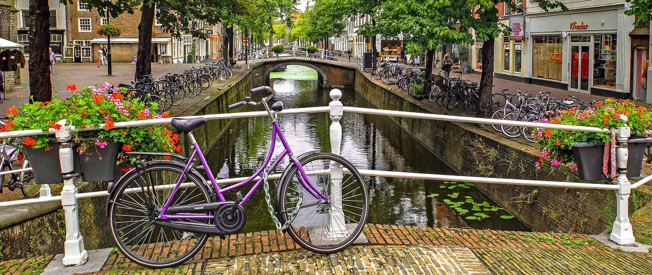 a view of a canal in the netherlands with a bike leaning against a bridge