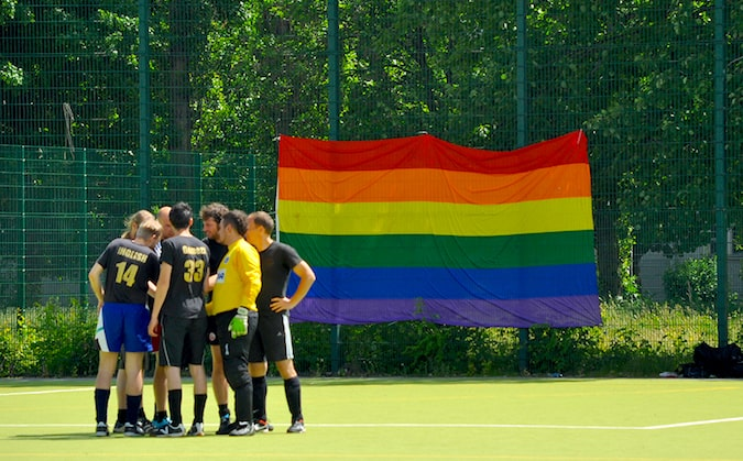 A soccer team standing on a field with a huge pride flag in the background