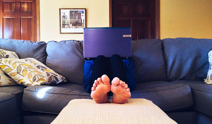 a person sitting on the couch with a laptop