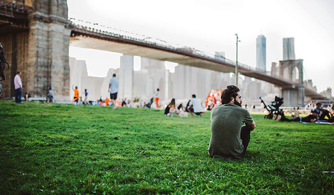 a man sitting alone in a park surrounded by people