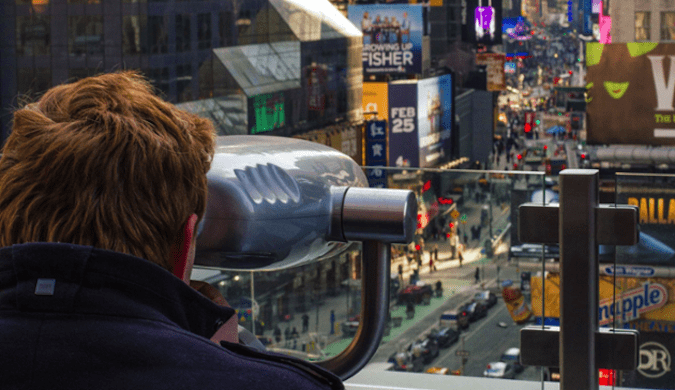 Man using the viewfinder to watch over the crowds of Times Square from above