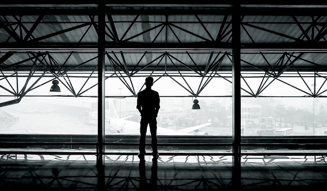 A man staring out of an airport window looking at airplanes